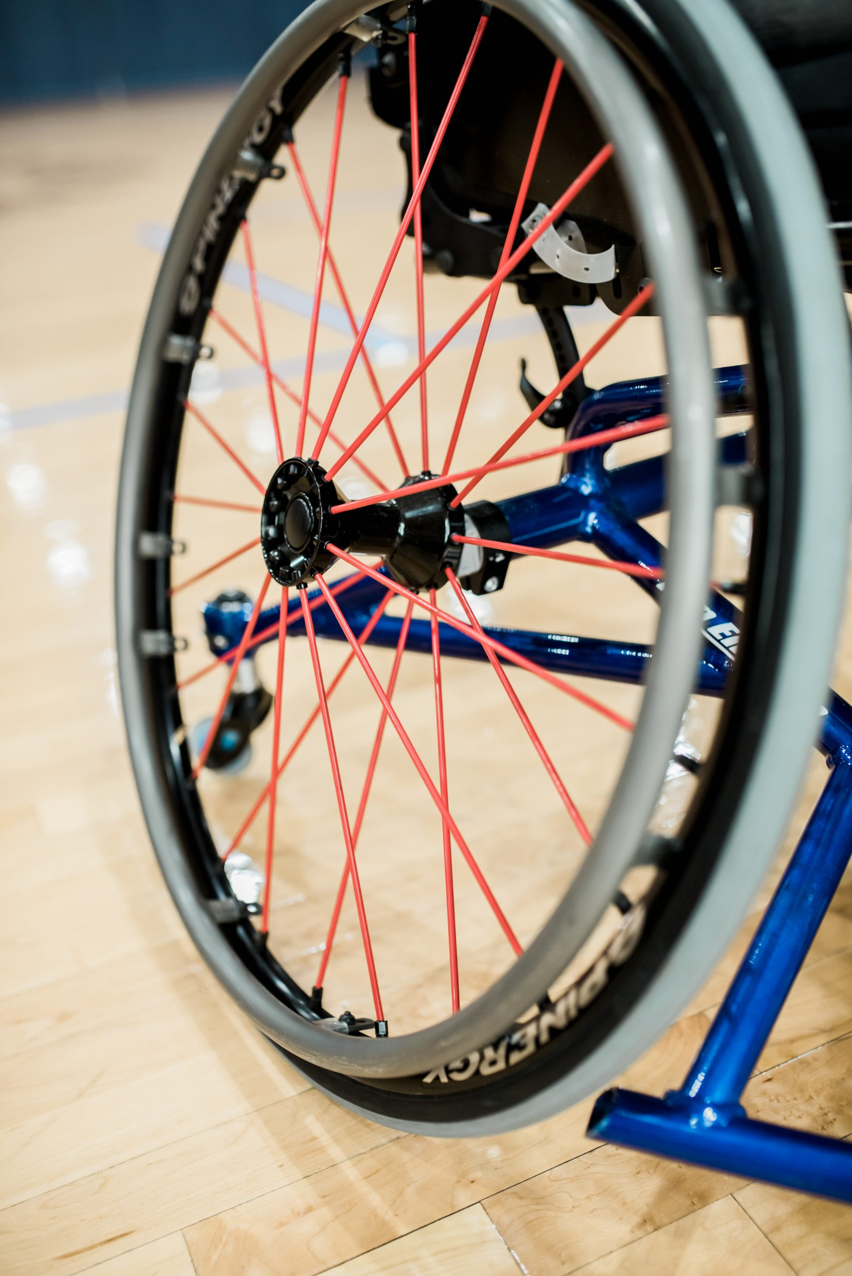 Close-up of big wheel of a sports wheelchair. Links to support and donation page.